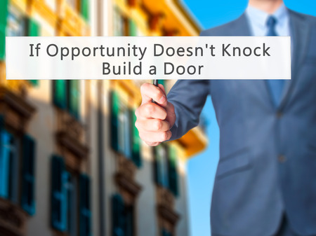 tocar la puerta: If Opportunity Doesnt Knock Build a Door - Businessman hand holding sign. Business, technology, internet concept. Stock Photo
