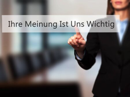 soliciting: Ihre Meinung Ist Uns Wichtig! (Your Opinion is Important to Us in German) - Businesswoman hand pressing button on touch screen interface. Business, technology, internet concept. Stock Photo