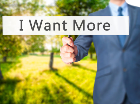 consumer rights: I Want More - Businessman hand holding sign. Business, technology, internet concept. Stock Photo