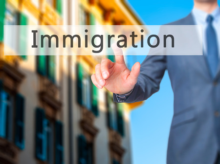 illegal immigrant: Immigration - Businessman hand pressing button on touch screen interface. Business, technology, internet concept. Stock Photo