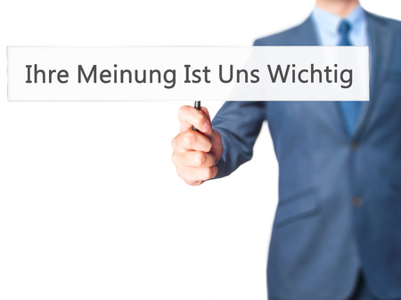 commenting: Ihre Meinung Ist Uns Wichtig! (Your Opinion is Important to Us in German) - Businessman hand holding sign. Business, technology, internet concept. Stock Photo