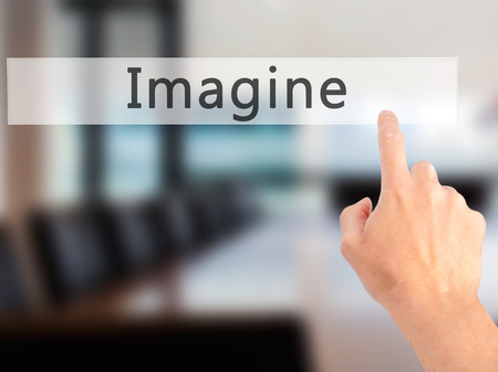 Imagine - Hand pressing a button on blurred background concept . Business, technology, internet concept. Stock Photo Stock Photo