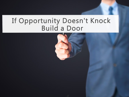 knock: If Opportunity Doesnt Knock Build a Door - Businessman hand holding sign. Business, technology, internet concept. Stock Photo