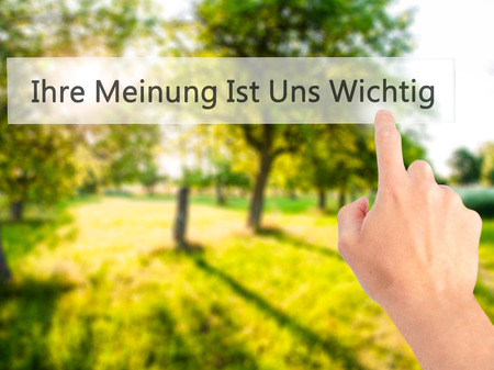 commenting: Ihre Meinung Ist Uns Wichtig! (Your Opinion is Important to Us in German) - Hand pressing a button on blurred background concept . Business, technology, internet concept. Stock Photo Stock Photo