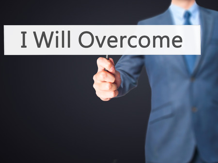 failed politics: I Will Overcome - Businessman hand holding sign. Business, technology, internet concept. Stock Photo