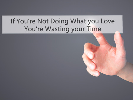 corporate waste: If Youre Not Doing What you Love Youre Wasting your Time - Hand pressing a button on blurred background concept . Business, technology, internet concept. Stock Photo