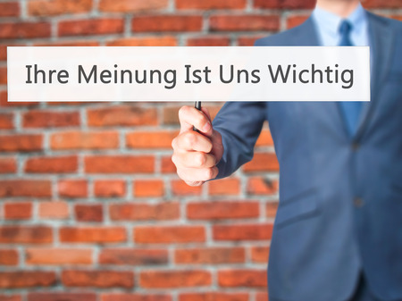 solicitation: Ihre Meinung Ist Uns Wichtig! (Your Opinion is Important to Us in German) - Businessman hand holding sign. Business, technology, internet concept. Stock Photo