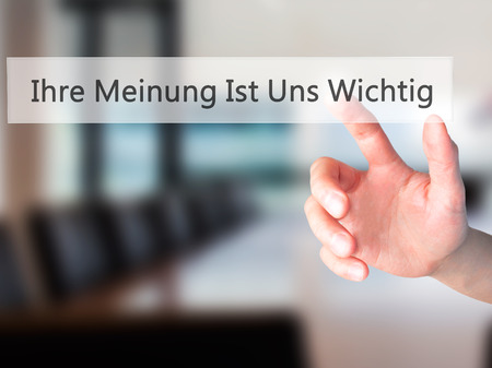 Ihre Meinung Ist Uns Wichtig! (Your Opinion is Important to Us in German) - Hand pressing a button on blurred background concept . Business, technology, internet concept. Stock Photo Stock Photo