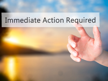 immediate: Immediate Action Required - Hand pressing a button on blurred background concept . Business, technology, internet concept. Stock Photo