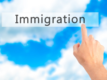 immigrate: Immigration - Hand pressing a button on blurred background concept . Business, technology, internet concept. Stock Photo