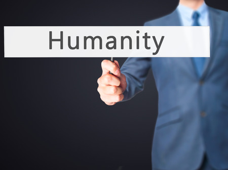 mercifulness: Humanity - Businessman hand holding sign. Business, technology, internet concept. Stock Photo Stock Photo