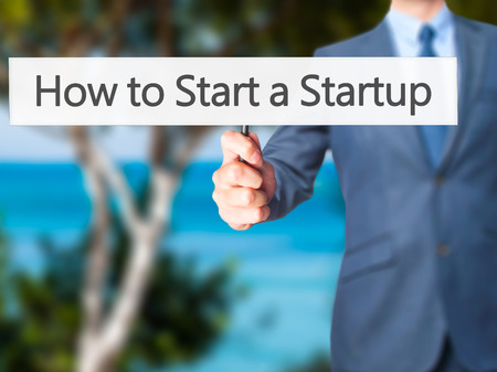 sucessful: How to Start a Startup - Businessman hand holding sign. Business, technology, internet concept. Stock Photo