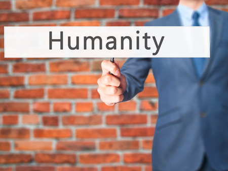 clemency: Humanity - Businessman hand holding sign. Business, technology, internet concept. Stock Photo Stock Photo