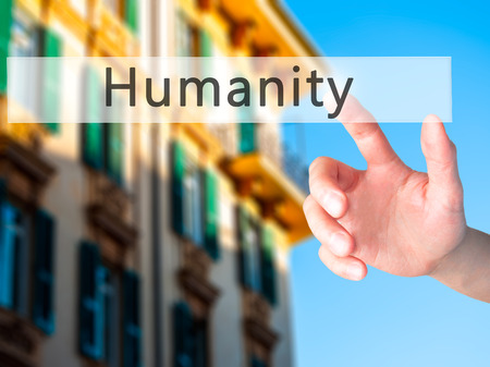 humanity: Humanity - Hand pressing a button on blurred background concept . Business, technology, internet concept. Stock Photo