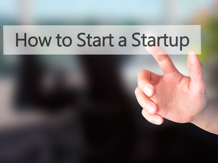 sucessful: How to Start a Startup - Hand pressing a button on blurred background concept . Business, technology, internet concept. Stock Photo