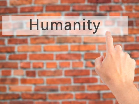 Humanity - Hand pressing a button on blurred background concept . Business, technology, internet concept. Stock Photo