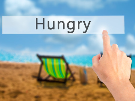 disgrace: Hungry - Hand pressing a button on blurred background concept . Business, technology, internet concept. Stock Photo