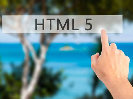 html 5: HTML 5 - Hand pressing a button on blurred background concept . Business, technology, internet concept. Stock Photo