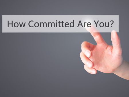 committed: How Committed Are You - Hand pressing a button on blurred background concept . Business, technology, internet concept. Stock Photo
