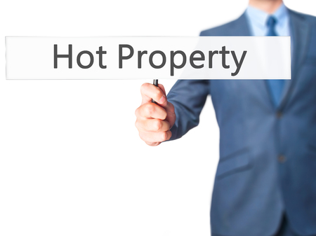 demanded: Hot Property - Businessman hand holding sign. Business, technology, internet concept. Stock Photo