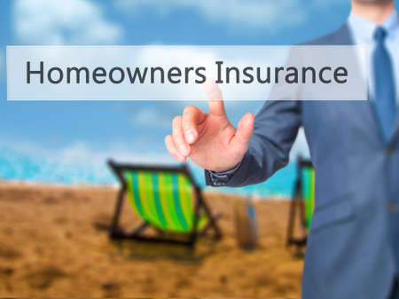homeowners: Homeowners Insurance - Businessman hand pressing button on touch screen interface. Business, technology, internet concept. Stock Photo