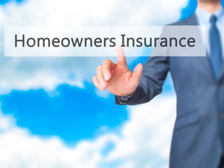 homeowners insurance: Homeowners Insurance - Businessman hand pressing button on touch screen interface. Business, technology, internet concept. Stock Photo