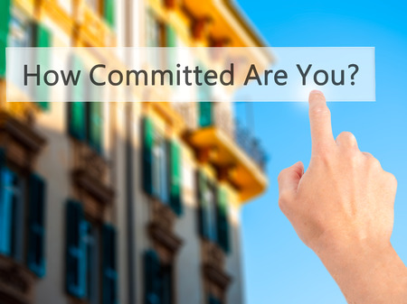 commitment committed: How Committed Are You - Hand pressing a button on blurred background concept . Business, technology, internet concept. Stock Photo