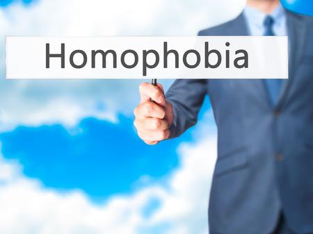 homophobia: Homophobia - Businessman hand holding sign. Business, technology, internet concept. Stock Photo