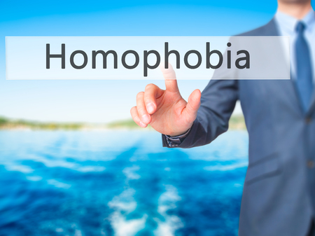 homophobia: Homophobia - Businessman hand pressing button on touch screen interface. Business, technology, internet concept. Stock Photo