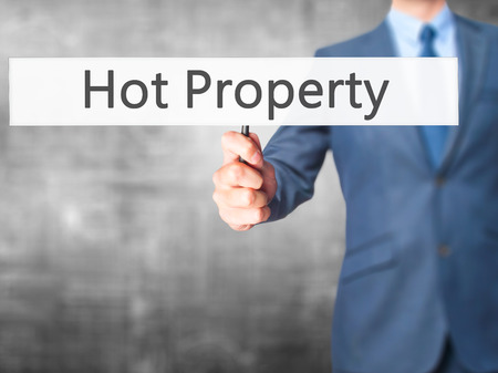 better price: Hot Property - Businessman hand holding sign. Business, technology, internet concept. Stock Photo