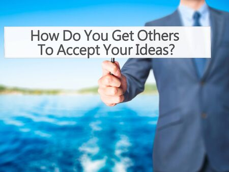 persuasiveness: How Do You Get Others To Accept Your Ideas - Businessman hand holding sign. Business, technology, internet concept. Stock Photo Stock Photo