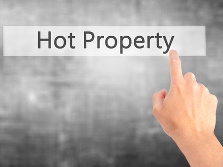 demanded: Hot Property - Hand pressing a button on blurred background concept . Business, technology, internet concept. Stock Photo