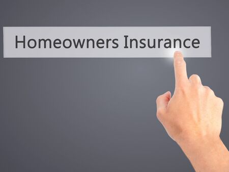 homeowners: Homeowners Insurance - Hand pressing a button on blurred background concept . Business, technology, internet concept. Stock Photo Stock Photo