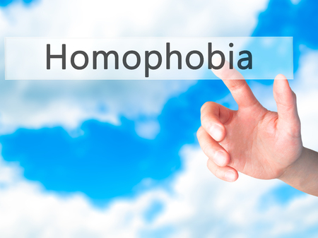 homophobia: Homophobia - Hand pressing a button on blurred background concept . Business, technology, internet concept. Stock Photo
