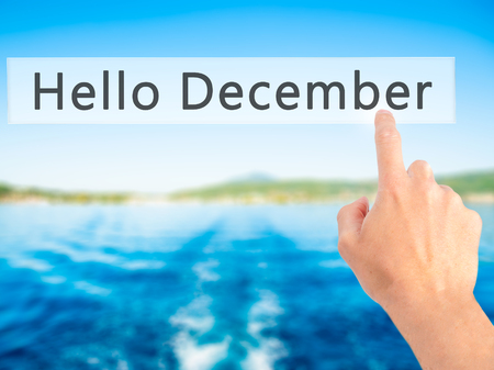 january 1: Hello December - Hand pressing a button on blurred background concept . Business, technology, internet concept. Stock Photo Stock Photo