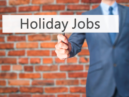 in need of space: Holiday Jobs - Businessman hand holding sign. Business, technology, internet concept. Stock Photo Stock Photo