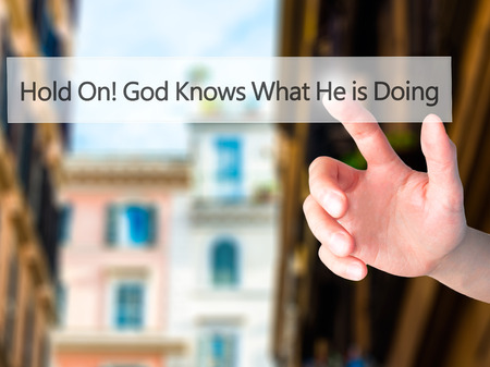 god button: Hold On God Knows What He is Doing - Hand pressing a button on blurred background concept . Business, technology, internet concept. Stock Photo
