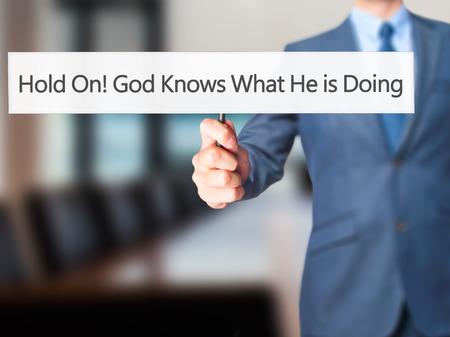 confessing: Hold On God Knows What He is Doing - Businessman hand holding sign. Business, technology, internet concept. Stock Photo