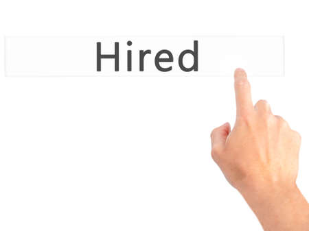 recruit help: Hired - Hand pressing a button on blurred background concept . Business, technology, internet concept. Stock Photo