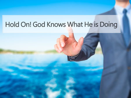 confessing: Hold On God Knows What He is Doing - Businessman hand pressing button on touch screen interface. Business, technology, internet concept. Stock Photo
