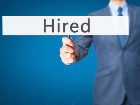 new recruit: Hired - Businessman hand holding sign. Business, technology, internet concept. Stock Photo Stock Photo