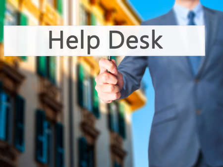 virtual assistant: Help Desk - Businessman hand holding sign. Business, technology, internet concept. Stock Photo