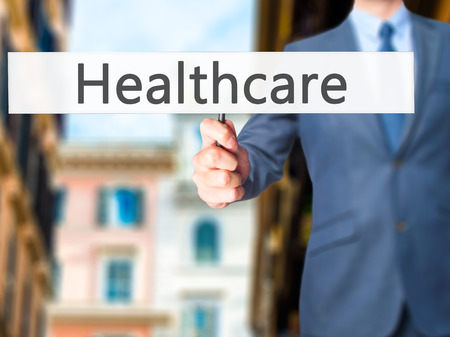 health care funding: Healthcare - Businessman hand holding sign. Business, technology, internet concept. Stock Photo