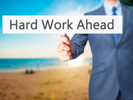 hard work ahead: Hard Work Ahead - Businessman hand holding sign. Business, technology, internet concept. Stock Photo Stock Photo