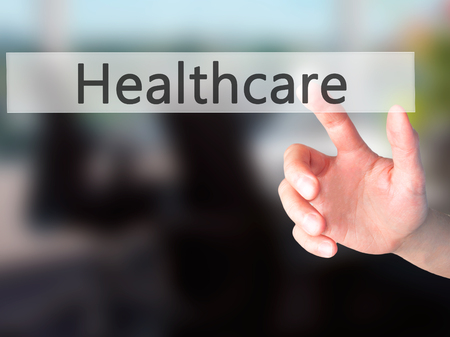 mandate: Healthcare - Hand pressing a button on blurred background concept . Business, technology, internet concept. Stock Photo