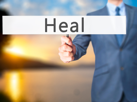 resonate: Heal - Businessman hand holding sign. Business, technology, internet concept. Stock Photo