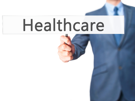 mandate: Healthcare - Businessman hand holding sign. Business, technology, internet concept. Stock Photo