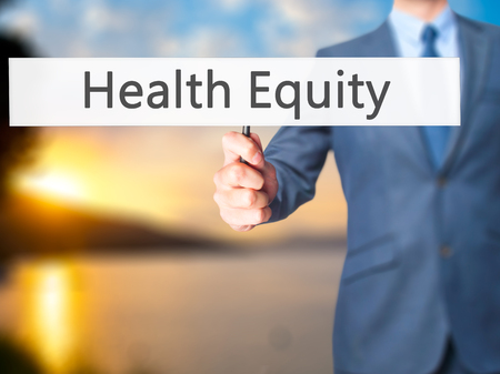 health equity: Health Equity - Businessman hand holding sign. Business, technology, internet concept. Stock Photo