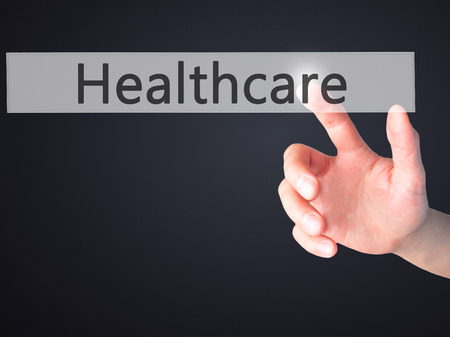 premiums: Healthcare - Hand pressing a button on blurred background concept . Business, technology, internet concept. Stock Photo