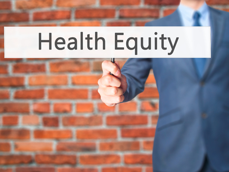 equity: Health Equity - Businessman hand holding sign. Business, technology, internet concept. Stock Photo